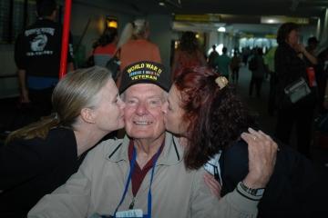 Veteran getting kissed on cheeks