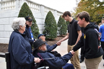 Student shaking hands with veterans