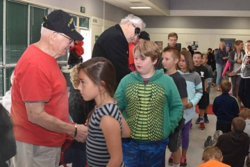 Veterans at a school shaking hands with students