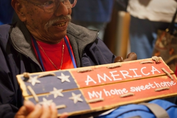 Veteran with America My Home Sweet Home sign