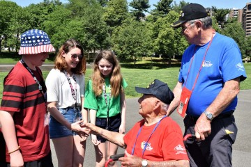 Kids shaking hands with a veteran