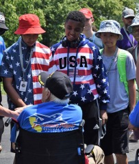 Veteran shaking hands with students