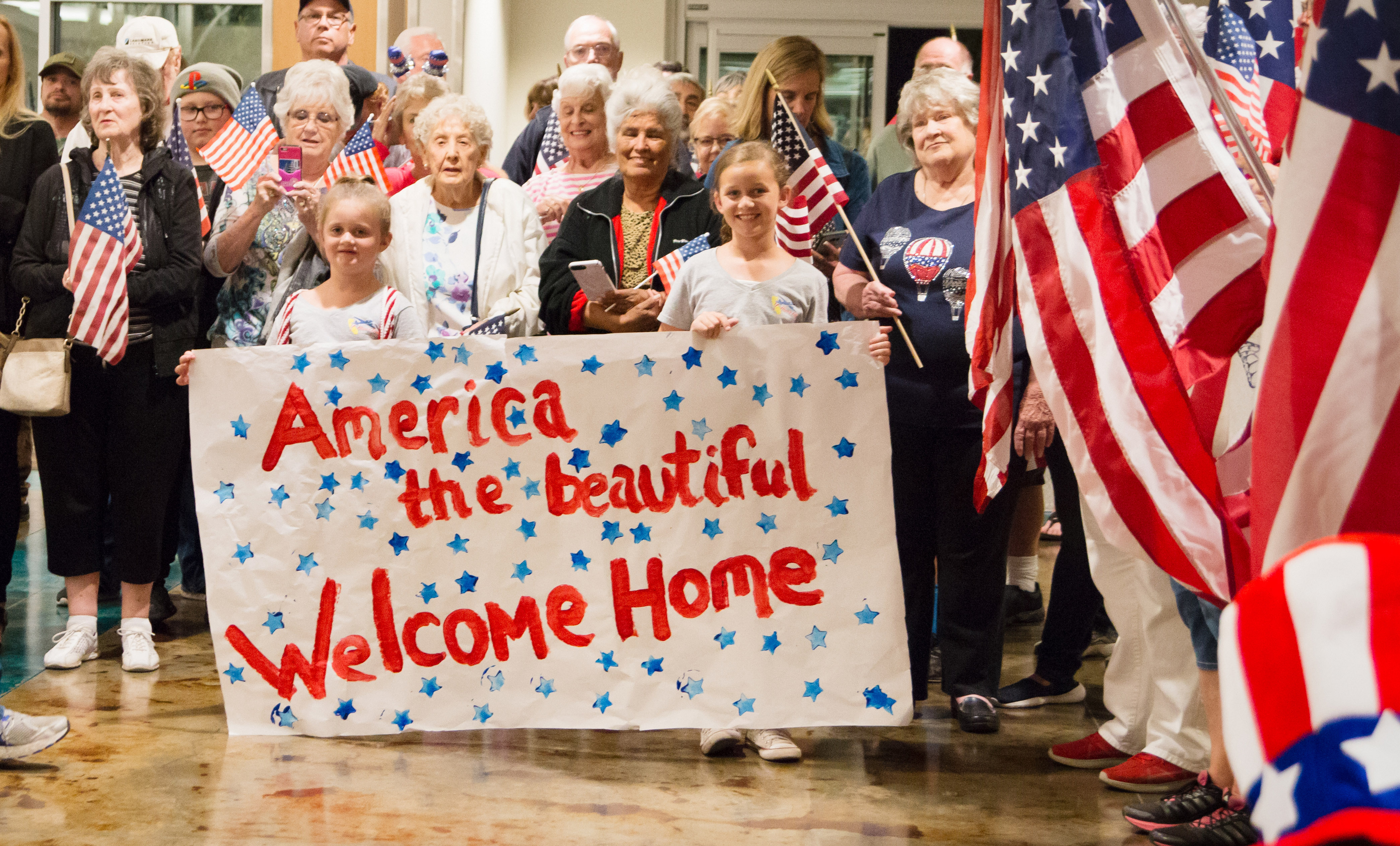 America the Beautiful Welcome Home banner at the airport